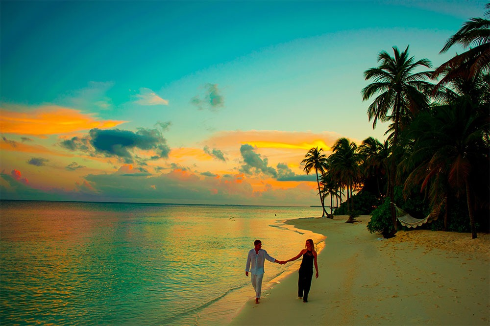 Man and Woman Holding Hands Walking on a Beach